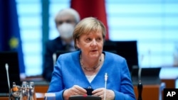 German Chancellor Angela Merkel removes her mask, at the beginning of a Federal Cabinet meeting at the Federal Chancellery, in Berlin, Sept. 8, 2021.
