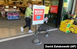 In this May 19, 2021, photo, a shopper pushes her basket filled with purchases past a sign warning of the need to wear face masks while in a food store in Aurora, Colorado. (AP Photo/David Zalubowski)