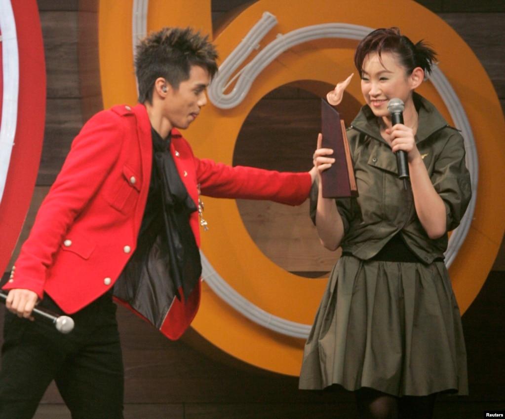 """歌手張敬軒(左)祝賀獲獎的香港歌手王菀之(2007年1月1日)。 張敬軒發表過支持香港雨傘運動的言論,被打成""""港獨""""歌手。 2017年1月9日,張敬軒在微博發表長文表示,自己出生在廣州,有身為中國人的驕傲,但被人杜撰了很多激烈言辭和資料,被戴上""""港獨""""帽子,受到攻擊。 他重申:""""我是一個中國人,我由始至終都不是'港獨',我堅決反對一切分裂國家的行為"""" 。 但1月25日中國國防報發表文章《決不允許藝人吃中國飯砸中國鍋》,指張敬軒早前被踢出湖南衛視《歌手》節目,是藝人因港獨言論而被除名的例子。 文章稱其行為是""""一邊在內地撈金、一邊辱華涉獨""""。"""