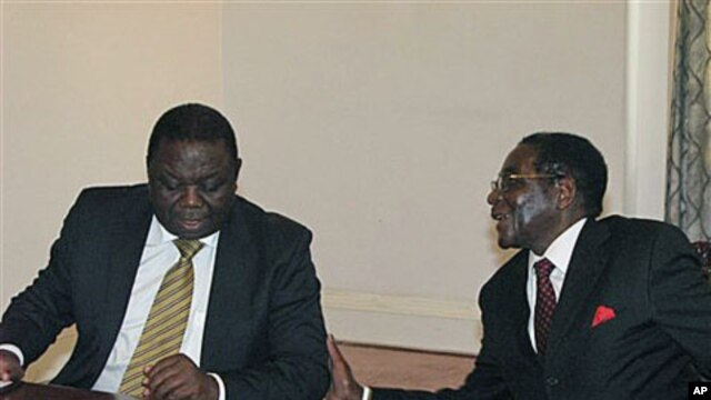 Zimbabwean President Robert Mugabe, right chats to Prime Minister Morgan Tsavangirai during their end of year press conference at State House in Harare, Dec 20, 2010