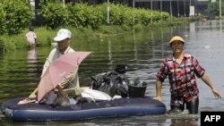 Cư dân Thái Lan lội qua 1 khu vực bị ngập lụt tại huyện Don Muang ở Bangkok, Thái Lan, 23/10/2011