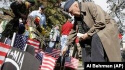 Seorang veteran Perang Dunia II di Amerika, menancapkan bendera di depan Memorial Veteran Vietnam dalam upacara Hari Veteran di Cincinnati, AS, 2013.