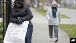 """Shena Hardin sostiene un rótulo que lee """"Sólo un idiota conduce sobre la acera para rebasar a un autobús escolar""""."""