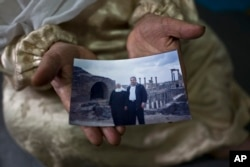 """FILE - Amineh Hamad, 58, a Syrian refugee from Eastern Ghouta, shows a photograph of herself and her husband Ali Abdulqader, 58, at her shelter in the Ritsona refugee camp, Greece, Jan. 7, 2017. """"It was the last time we visited the Roman site of Busra al-Sham. ...We miss these days. We hope one day it will come back,"""" Amineh said."""