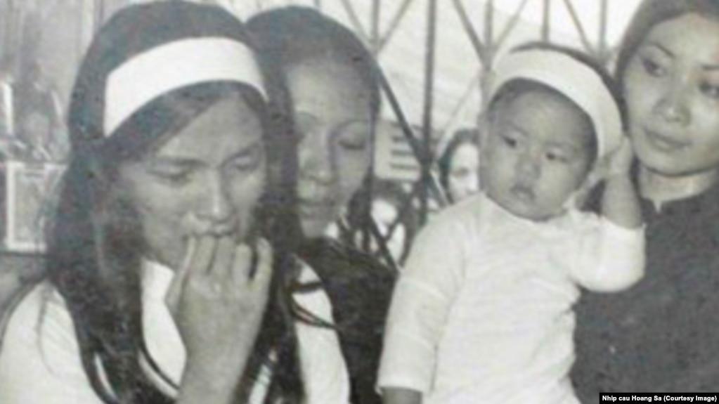 Bà Huỳnh Thị Sinh (trái) trong lễ tang chồng.