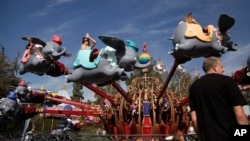 FILE - Visitors ride the Dumbo the Flying Elephant ride at Disneyland in Anaheim, California, Jan. 22, 2015.