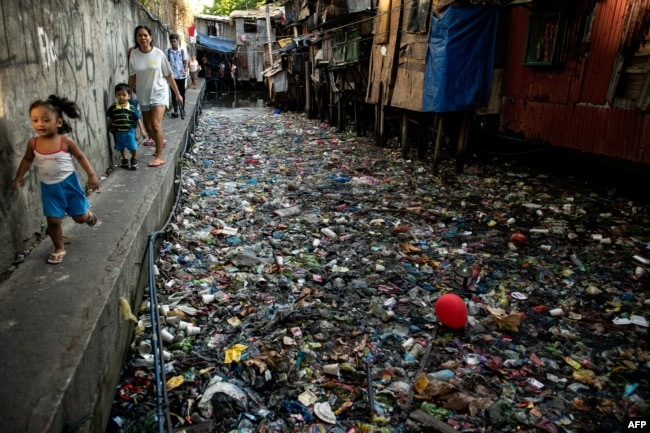 People walk along a canal polluted with plastic and garbage at the Estero de San Lazaro in Manila in the Philippines on March 22, 2019.