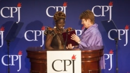 Mae Azango receiving CPJ award from AP Executive Editor Kathleen Carroll