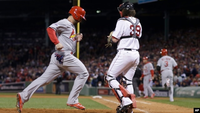 St. Louis Cardinals' Daniel Descalso scores past Boston Red Sox catcher Jarrod Saltalamacchia (39) on a hit by Carlos Beltran during the seventh inning of Game 2 of baseball's World Series, Oct. 24, 2013,