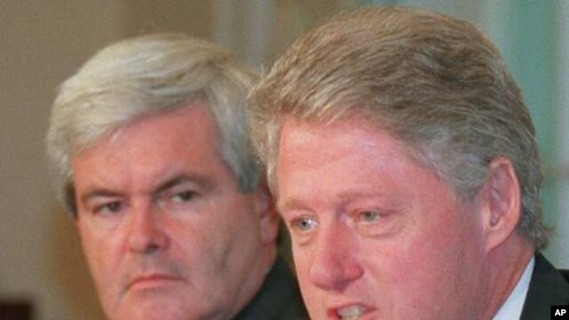 House Speaker Newt Gingrich (left) looks on as President Clinton talks to reporters in the Cabinet Room of the White House, July 29, 1996 (file photo)