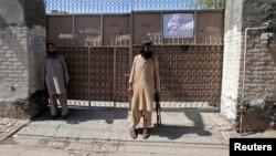 Nhân viên bảo vệ với khẩu AK-47 đứng canh trước cổng nhà của thủ lãnh nhóm Lashkar e-Jhangvi