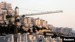 FILE - A construction crane is seen next to homes in the Har Homa Jewish settlement in Jerusalem.