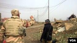 Soldados iraquíes avanzan hacia el frente de batalla mientras familias huyen en Mosul. Enero 23, 2017. (H. Murdock/VOA)