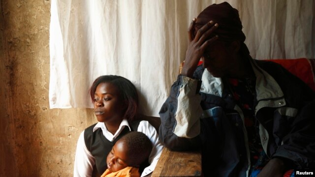 An HIV-AIDS patient (R) places her hand on her forehead during a visit by a caregiver at her home in Matero township on the outskirts of Lusaka, Zambia, April 17, 2012.