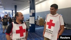 Marco Franco, left, deputy director of Mexican Red Cross disaster relief, talks with Gustavo Santillan, who is part of a group of 33 Mexican Red Cross volunteers helping at the George R. Brown convention center in Houston, Texas, Sept. 4, 2017.