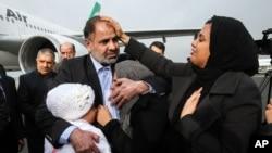 Nhà ngoại giao Iran Ahmad Nour Nikbakht bị bắt cóc tại Yemen vào năm 2013 ôm vợ con tại sân bay Mehrabad sau khi được trả tự do tại Tehran, ngày 5/3/2015.