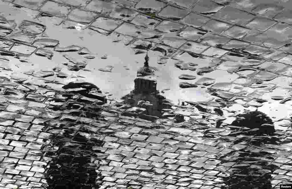 Odraz bazilike Svetog Petra u lokvi nakon kiše na istoimenom vatikanskom trgu nekoliko sati prije obraćanja pape Benedicta 16. vjernicima.