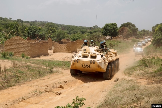 FILE - United Nations peacekeeping force vehicles drive by houses destroyed by violence in September, in the abandoned village of Yade, Central African Republic, April 27, 2017.