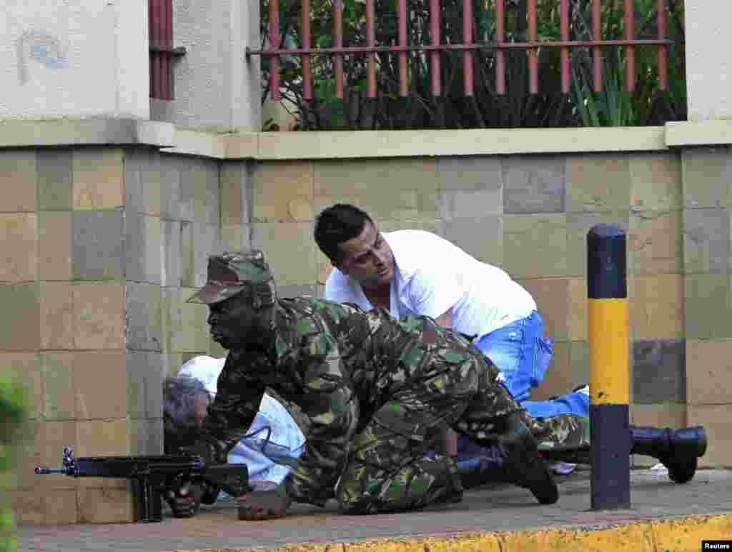2013年9月21日,在内罗毕遭到袭击的韦斯特盖特购物中心,一名肯尼亚士兵用一堵墙作掩护。
