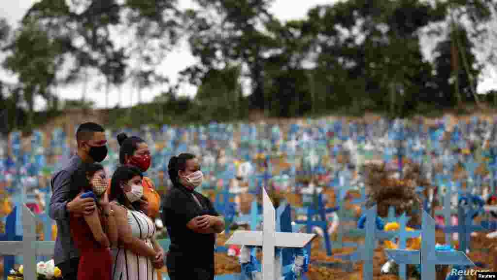 브라질 아마조나스 마나우스의 파르쿠 타루마 묘지에서 신종 코로나바이러스 감염증(COVID-19)으로 숨진 희생자의 가족들이 마스크를 착용한 채 애도하고 있다.