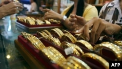 Myanmar vendors arranging a display of gold jewellery at a jewellery shop at Chinatown in downtown Yangon. Housewives huddle over jewellery counters in Yangon's bustling Chinatown -- but they do not have fashion o