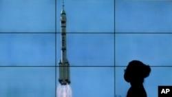 在北京,一名戴口罩的女子從電視屏幕前走過,電視屏幕上播放著搭載神舟十二號載人飛船的長征二號F遙十二運載火箭從酒泉衛星發射中心升空的景象。(2021年6月17日)