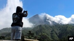 Seorang pengunjung menggunakan kamera ponsel untuk mengambil foto Gunung Merapi di Cangkringan, Yogyakarta, Selasa, 22 Mei 2018.