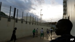 FILE - Migrants play soccer inside a temporary camp, after a fiery shipwreck of a fishing boat packed with 500 migrants from Eritrea, in Lampedusa, Italy, Oct. 6, 2013.