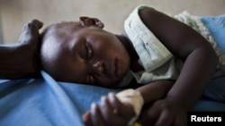 FILE - A young girl with malaria rests in the inpatient ward of the Malualkon Primary Health Care Center in Malualkon, in the South Sudanese state of Northern Bahr el-Ghazal, June 1, 2012.