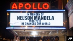Pedestrians pass beneath the Apollo Theater marquee commemorating the life of South African leader Nelson Mandela in the Harlem neighborhood of New York, Dec. 5, 2013.