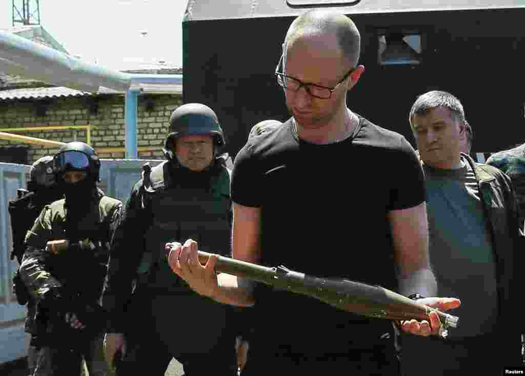 Prime Minister Arseny Yatseniuk inspects weapons seized from pro-Russian separatists as he meets with Ukrainian servicemen in the eastern town of Slovyansk, July 16, 2014.