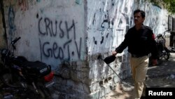Policeman walks past graffiti directed at local media house Geo TV, Karachi, May 20, 2014.
