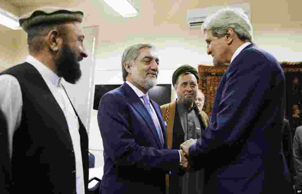 Afghan presidential candidate Abdullah Abdullah, center, shakes hands with U.S. Secretary of State John Kerry at the start of a meeting at the U.S. Embassy in Kabul, July 11, 2014.