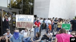 A group of demonstrators sit outside the entrance to the National Air and Space Museum in Washington after police pepper-sprayed a group of protestors trying to get into the museum Saturday, Oct. 8, 2011.