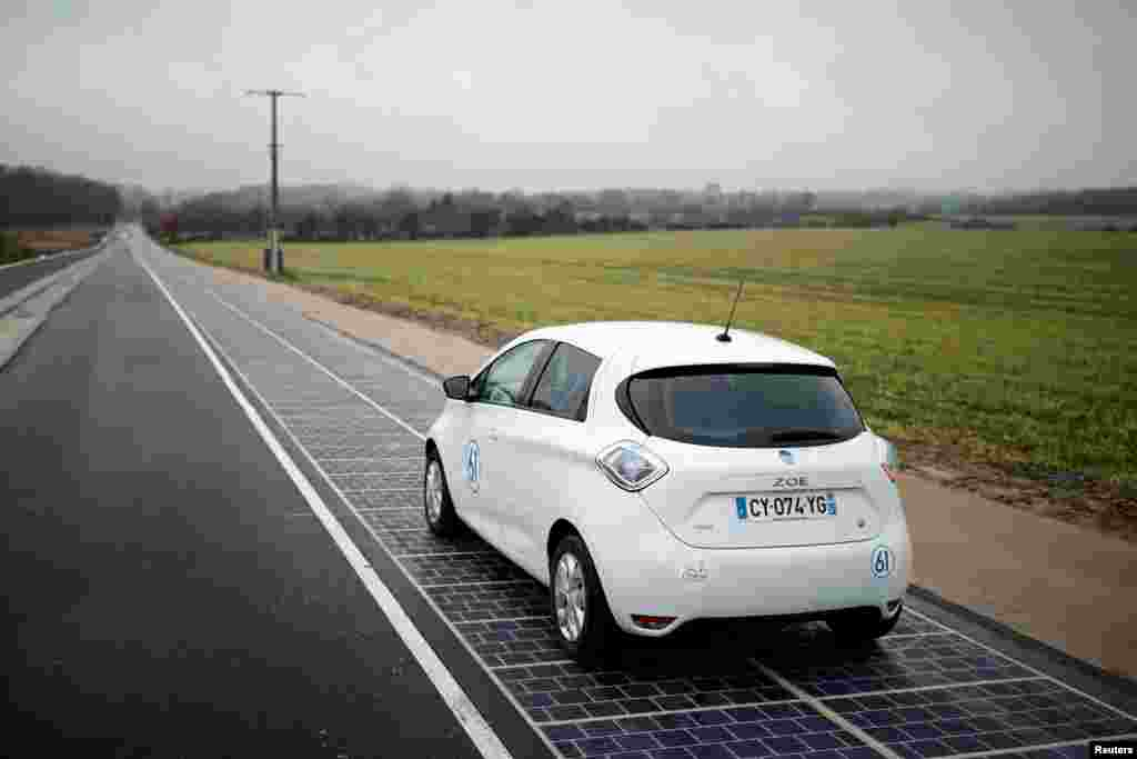An automobile drives on a solar panel road during its inauguration in Tourouvre, Normandy, northwestern France.