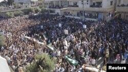 Warga Suriah mengusung peti jenazah para korban serangan tentara Suriah di Daraa menuju tempat pemakaman (9/6).
