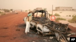 A man takes a close look at a burned-out truck in Timbuktu, Mali, January 31, 2013.