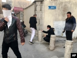 FILE - In this photo taken by an individual not employed by the Associated Press and obtained by the AP outside of Iran, people are affected by tear gas fired by anti-riot Iranian police to disperse demonstrators in a protest over Iran's weak economy, in