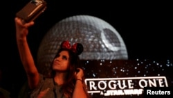 "A guest takes a selfie as the Spaceship Earth is turned into the Death Star via projectors in advance of the release of the new Star Wars movie ""Rogue One,"" at the Walt Disney World's Epcot Center in Lake Buena Vista, Florida, Dec. 5, 2016."