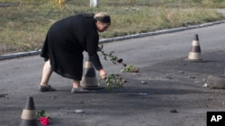 A woman puts flower on the ground in the spot where shell landed killing several people, in Sartana, on the outskirts of the town of Mariupol, eastern Ukraine, Oct. 15, 2014.