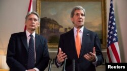 Britain's Foreign Secretary Phillip Hammond, left, and U.S. Secretary of State John Kerry deliver a statement at a press conference in London, Feb. 21, 2015.