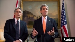 Ngoại trưởng Anh Phillip Hammond và Ngoại trưởng Hoa Kỳ John Kerry (phải) phát biểu tuyên bố tại một cuộc họp báo ở London, 21/2/2015.