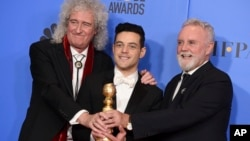 "Brian May, left, and Roger Taylor, right, of Queen, and Rami Malek pose with the award for best motion picture, drama for ""Bohemian Rhapsody"" at the 76th annual Golden Globe Awards on Sunday, Jan. 6, 2019, in Beverly Hills, Calif."
