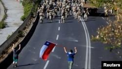 20일 칠레 수도 산티아고에서 반정부 시위 참가자들이 전진하는 군인들과 대치하고 있다.
