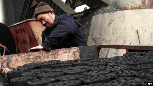 A worker stacks coal briquettes at a coal distribution business in Huaibei, central China's Anhui province, January 30, 2013.