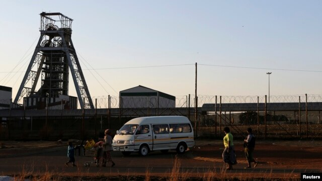Members of the mining community walk past the Doornkop Gold Mine, about 30 km (19 miles) west of Johannesburg, September 3, 2013.