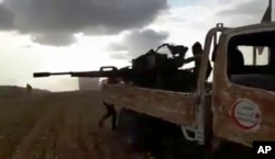 This frame grab from video provided by Baladi News Network, a Syrian opposition media outlet, is said to show Turkey-backed Syrian opposition fighters fire their weapons during clashes near the northern Syrian town of al-Bab, Aleppo province, Syria.