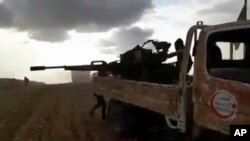 This frame grab from video provided by Baladi News Network, a Syrian opposition media outlet, is said to show Turkey-backed Syrian opposition fighters fire their weapons during clashes near the northern Syrian town of al-Bab, Aleppo province, Syria, Feb. 9, 2017.