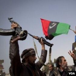 Para tentara pemberontak merayakan kemenangan mereka di Ajdabiya, Sabtu (24/3).