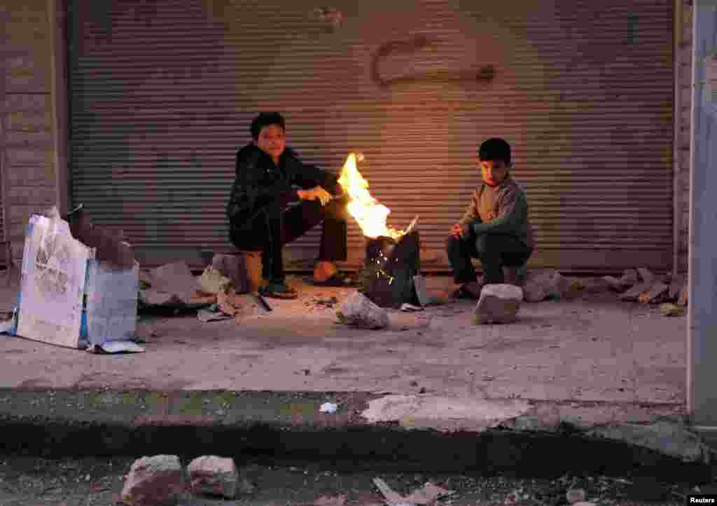 Boys warm up next to a fire outside a building in the Ain Tarma neighborhood of Damascus, Syria, February 5, 2013.